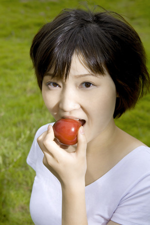 raised viewpoint: Girl eating apple on lawn