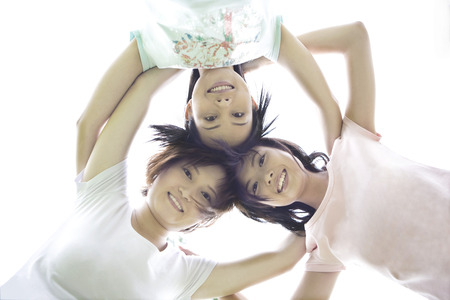 non moving activity: Three girls on lawn with head to head Stock Photo