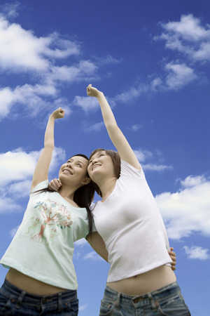 raised viewpoint: Two girls hugging under the blue sky
