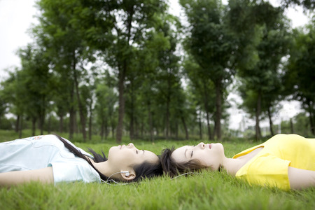 non moving activity: Two girls lying on lawn listening music Stock Photo