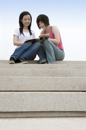 non moving activity: Two girls sitting on the stone steps reading books