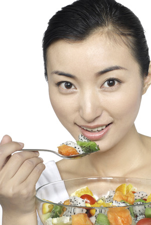 Woman eating fruit with spoon