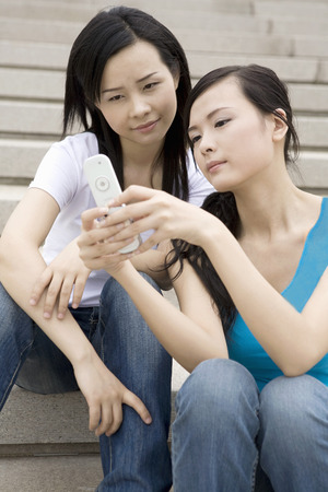 staircases: Two girls sitting on the stone steps playing mobile phone