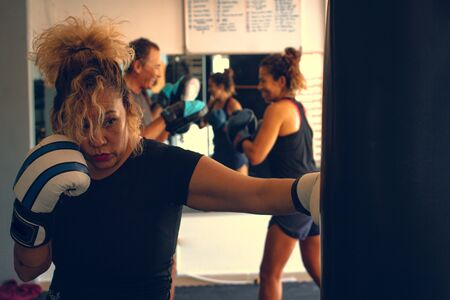 Blonde woman practicing boxing jab with blue and white gloves punching a boxing bag in a gym