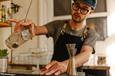 Waiter with apron, glasses and a cap transferring liquid into a glass with ice to an icy cocktail glass in a stylish bar