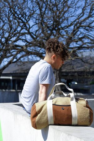 Vertical photo of the profile of a man with a modern hairstyle sitting on a wall with a vintage sports bag next to it in front of a tree