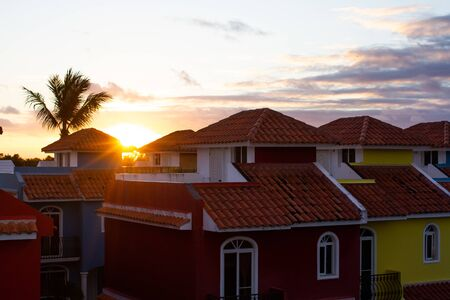 Sunset from a colorful neighborhood of luxurious houses with red roofs and a palm tree protruding from the roof