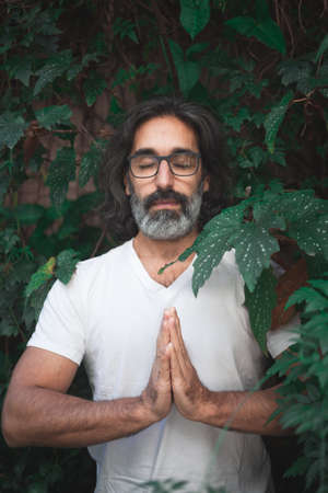 Vertical photo of the portrait of a man in white with long gray hair and glasses standing on a garden with his hands together in meditation