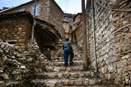Anonymous Kurdish man in traditional pants and leather jacket climbs stone steps in traditional village of Palangan, Kurdistan, Iran Stock Photo