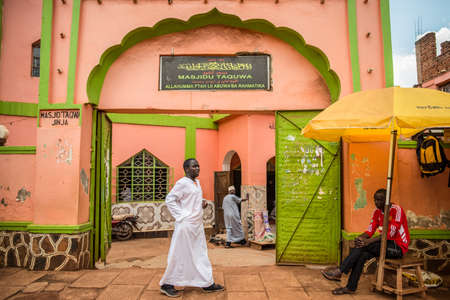 Jinja / Uganda - September 15, 2016: African Muslim men at the entrance arch to colorful pastel colored mosque