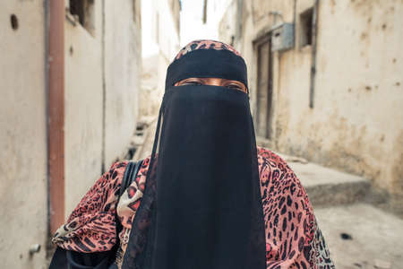 Portrait of adult Muslim woman wearing conservative niqab, only eyes visible, in Lamu island town