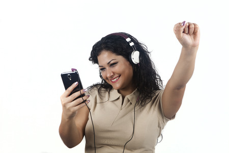 woman fist: Young brunette woman with raised fists listening to music with mobile Stock Photo