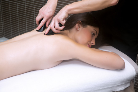 eyes open: brunette with eyes open in the spa getting back massage