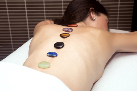 brunets: Smiling brunet in spa getting massage with hot stones
