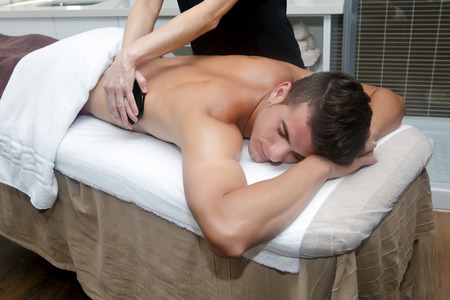 hot stones: Smiling brunet in spa getting massage with hot stones