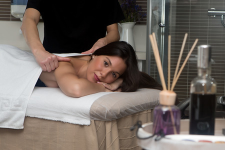 eyes open: Brunette with eyes open in spa getting back massage