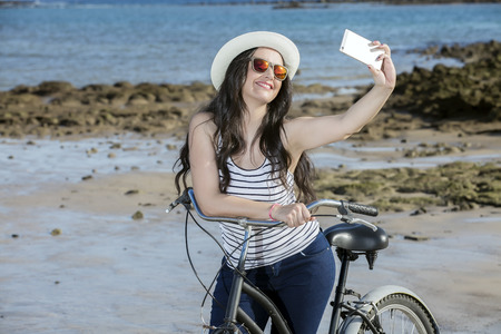 gran canaria: Young happy female in sunglasses with bicycle taking selfie on coast in Lanzarote, Spain.