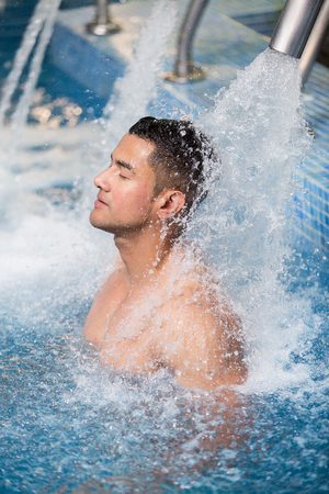 Vertical indoors shot of man with eyes closed refreshing under shower in pool. Stock Photo