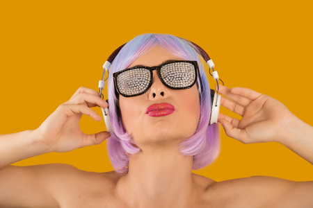 Bright rebellious girl in wig and glam sunglasses listening to music confidently.