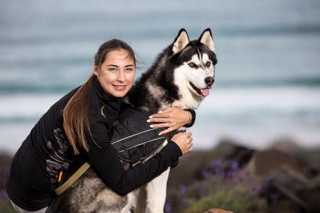 Content sportive woman hugging beautiful purebred Husky dog chilling on coastline.