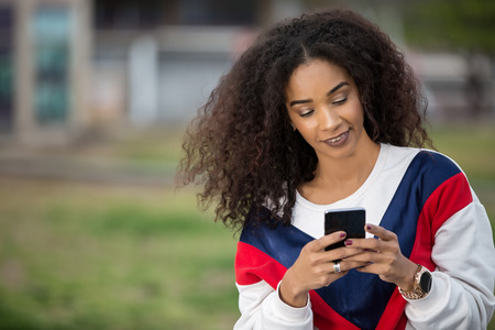 Adult trendy ethnic woman with curls standing on street and browsing smartphone in leisure.