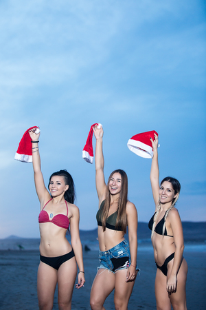 Confident models in bikinis holding hands up with Santa caps laughing at camera.