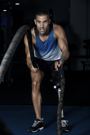 Adult confident sportsman with leg prosthesis working out with battling ropes