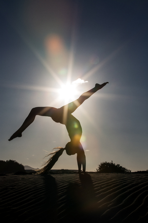 Female silhouette doing handstand yoga pose on beach in bright back lit
