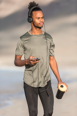 Young African American male with cup of hot beverage and modern smartphone listening to music and looking away while standing on blurred background of coast and sea Banco de Imagens