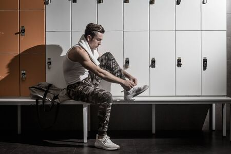 Side view of muscular guy in sportswear tying laces on sneakers while sitting on bench near lockers in gym changing room