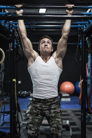 Focused muscular athlete hanging on bar and looking up while performing pull ups during training in modern gym