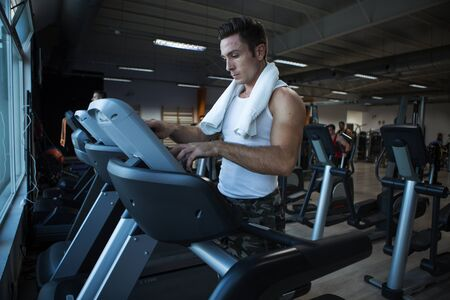 Strong male athlete with towel pushing buttons on treadmill during training in modern gym Zdjęcie Seryjne