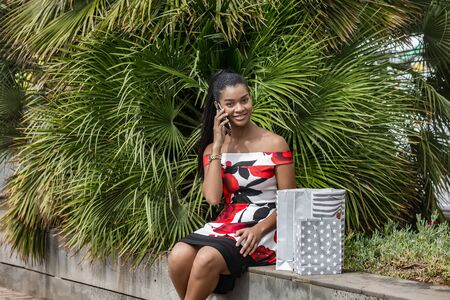 Contented African American female in colorful dress with paper bags phoning with smartphone while sitting on stone bench and looking at camera after shopping against green exotic plants on street