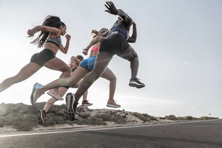 High angle of unrecognizable multiethnic female friends in sportswear sitting on road during running session