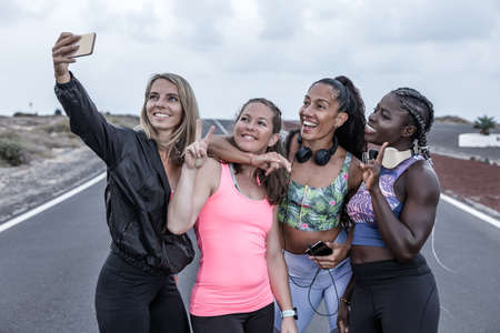 Ground level of anonymous multiethnic women in sportswear running fast on asphalt road during training in outskirts Banque d'images