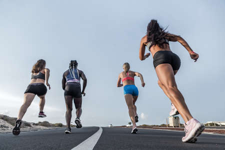 Ground level of anonymous multiethnic women in sportswear running fast on asphalt road during training in outskirts