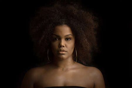 Confident young curly haired African American female with perfect makeup and hoop earrings and necklace looking at camera against black background