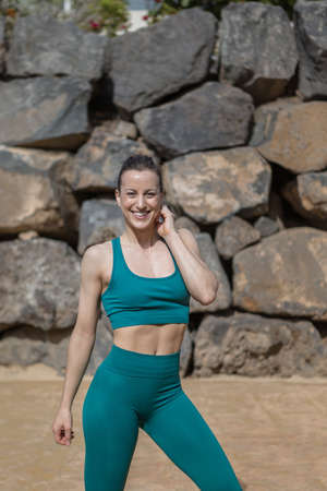 Delighted slim female in sportswear smiling for camera and touching neck while standing against stone wall