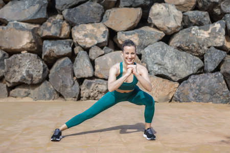 Positive female athlete in sportswear smiling for camera and doing Side Lunge against stone wall during fitness training