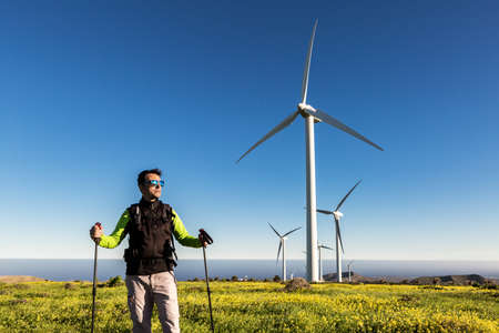 Peaceful male traveler with trekking sticks standing in meadow on background of windmills on Lanzarote