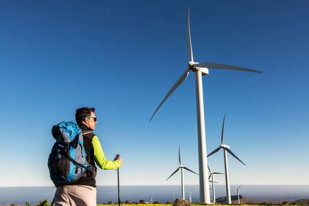 Back view of male discoverer with backpack and trekking poles standing on hill with big windmills against blue cloudless sky on Lanzarote