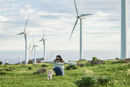 Content female owner playing with cute little dog in field on background of windmills on Lanzarote