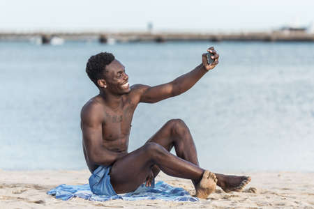 Full body of optimistic African American guy smiling and taking selfie while resting on beach near sea in summer on Lanzarote island, Spain