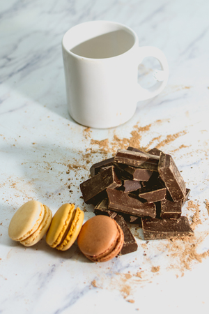 Tasty sweet macarons with cup of coffee on chocolate background and mountain on white background