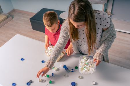 kids recycling and selecting plastic for recycling in garage or warehouse, fun, games