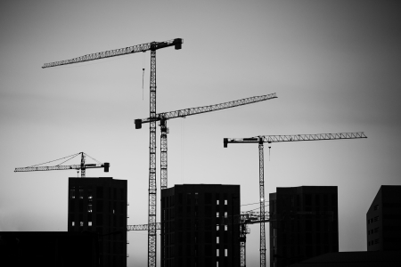 Cranes at sunset. Industrial construction cranes and building silhouettes over sun at sunrise. Black and white image.