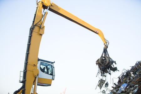 Crane grabber loading metal rusty scrap in the dock Standard-Bild