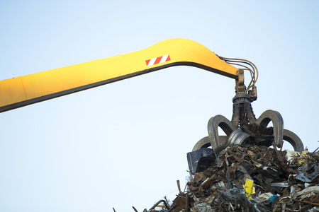 tracked: Large tracked excavator working a steel pile at a metal recycle yard