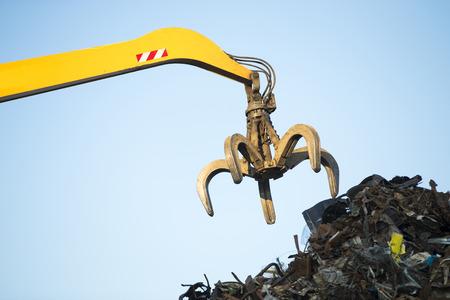 junkyard: Excavadora seguido trabajando un mont�n de acero en un patio de reciclaje de metal
