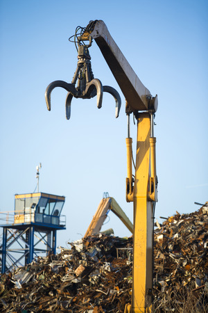 recycling center: Crane claw on top of pile with scrap metal in recycling center